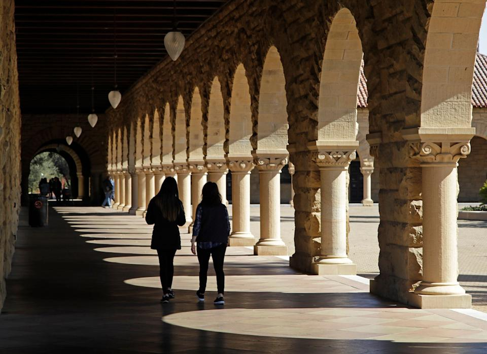 FILE- In this March 14, 2019, file photo students walk on the Stanford University campus in Santa Clara, Calif. Before student loans, people who couldn't afford to go to college usually didn't. Even though tuition was cheaper, it was still cost-prohibitive for many, who turned to solutions such as working through school, getting help from their parents or finding scholarships. (AP Photo/Ben Margot, File)