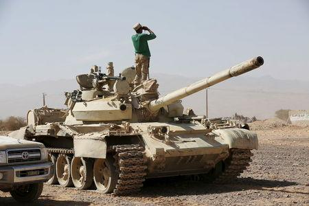 A soldier loyal to Yemen's President Abd-Rabbu Mansour Hadi stands atop a tank as he uses binoculars in Majaz district, in the country's northwestern provinceo of Marib, after the pro-Hadi forces took the area from Houthi rebels, December 18, 2015. REUTERS/Ali Owidha