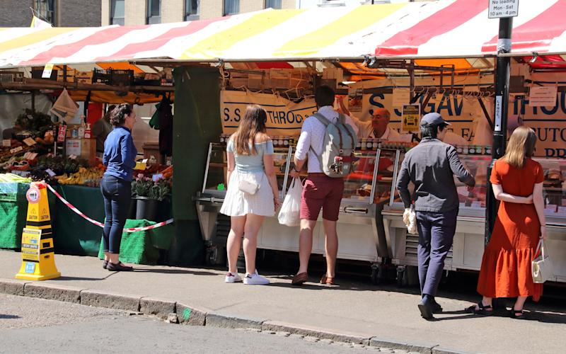 People in a queue practise social distancing as they wait to be served at an outdoor market stall during the coronavirus crisis. The UK government relaxed the guidelines on coronavirus lockdown, allowing people to spend more time outdoor as the death rate continues to drop. (Photo by Keith Mayhew / SOPA Images/Sipa USA)