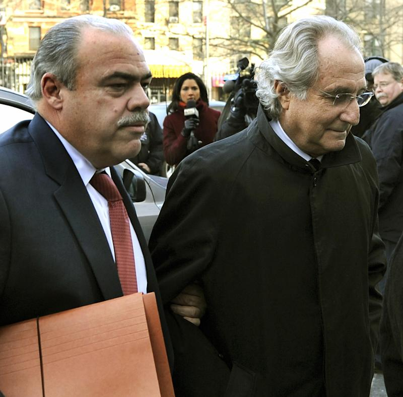 Bernard L. Madoff (R) arrives at US Federal Court for hearing regarding his bail January 14, 2009 in New York. Prosecutors are seeking a reversal of another judge's ruling on Monday that Madoff should be allowed to remain free under house arrest in his luxury Manhattan apartment. Prosecutors say Madoff violated his bail conditions by attempting to distribute more than a million dollars worth of jewelry to friends and relatives, when all his assets are under a court-ordered freeze. AFP PHOTO / TIMOTHY A. CLARY (Photo credit should read TIMOTHY A. CLARY/AFP via Getty Images)