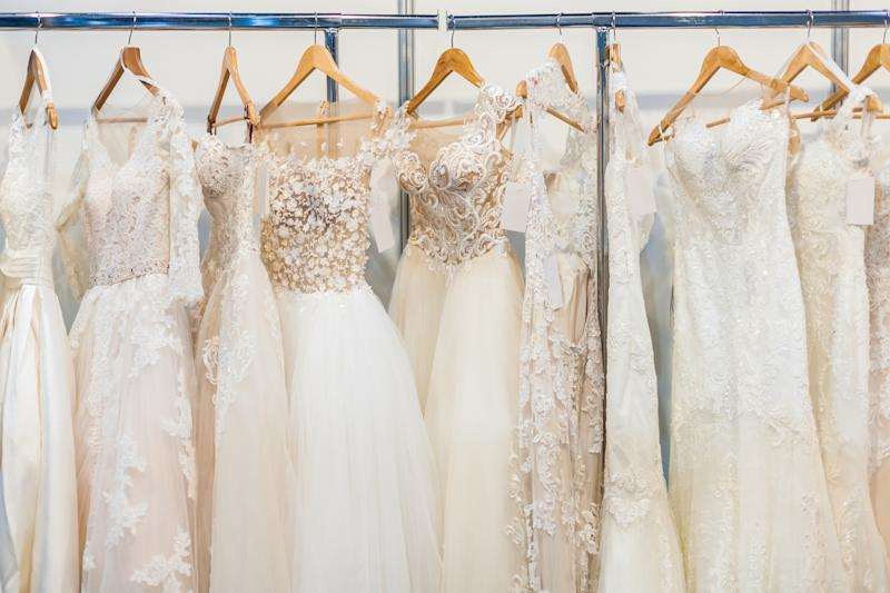 Many beautiful wedding dresses hang in the store