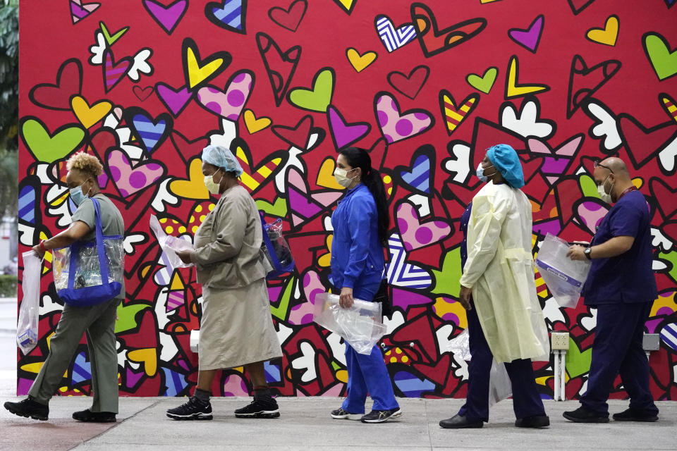 FILE - In this Sept. 22, 2020, file photo, healthcare workers line up for free personal protective equipment in front of a mural by artist Romero Britto at Jackson Memorial Hospital in Miami. The pandemic began with devastation in the New York City area, and was followed by a summertime crisis in the Sun Belt. But it is now striking cities with much smaller populations, often in conservative corners of America where anti-mask sentiment runs high, creating problems at hospitals and schools in the Midwest and West. (AP Photo/Wilfredo Lee)