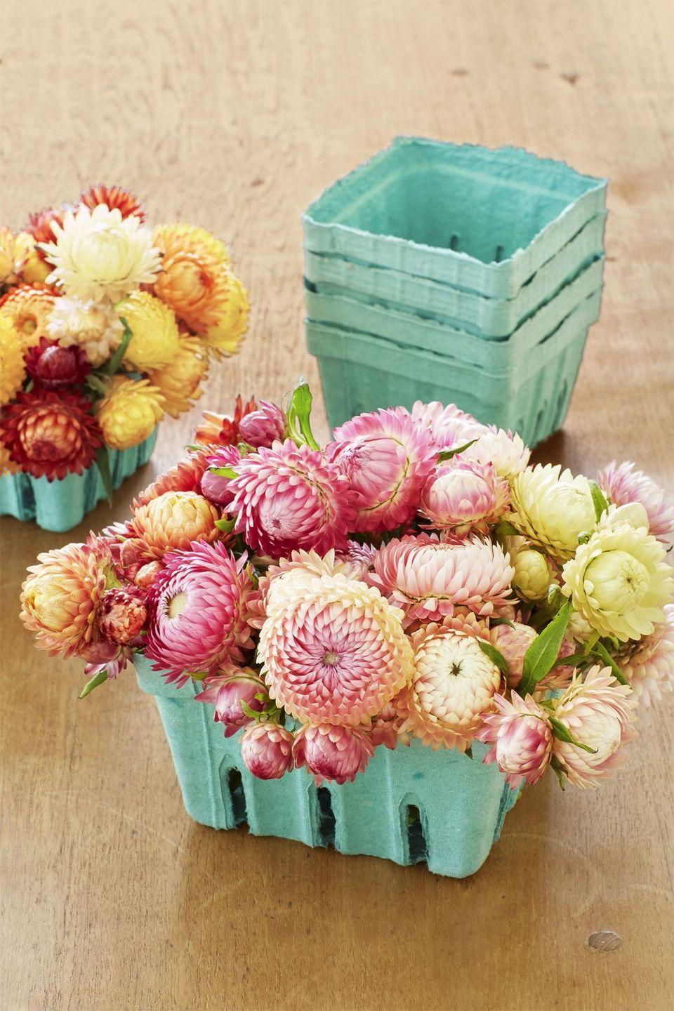 <p>While a centerpiece makes a bold statement, scattered floral arrangements can also make a big impact. Turn your leftover berry baskets into vases that perfectly fit a medley of hydrangeas, ranunculuses, and peonies. </p>