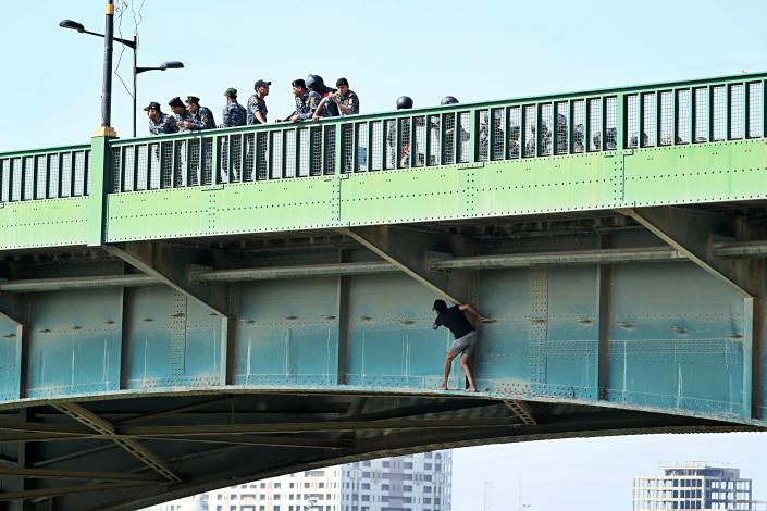 An anti-government protester tries to sneak while Iraqi security forces close the bridge leading to the Green Zone during a demonstration in Baghdad, Iraq, Saturday, Oct. 26, 2019. (Photo: Hadi Mizban/AP)