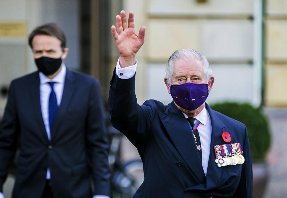 The British heir to the throne Prince Charles, Prince of Wales, who wears a mouth-and-nose cover, greets onlookers as he leaves the Hotel Adlon in Berlin, Sunday, Nov.15, 2020. Prince Charles and his wife, the Duchess of Cornwall, are in Berlin on the occasion of the central commemoration of the Volkstrauertag. This year's national day of mourning in memory of the victims of National Socialism and the dead of both world wars is dedicated to German-British friendship. (Christoph Soeder/dpa via AP)