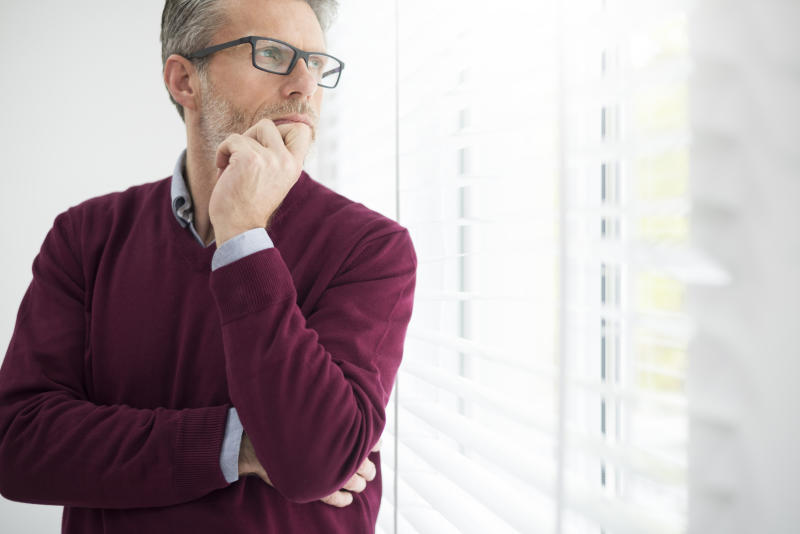 Man thinking hard while looking out a window.