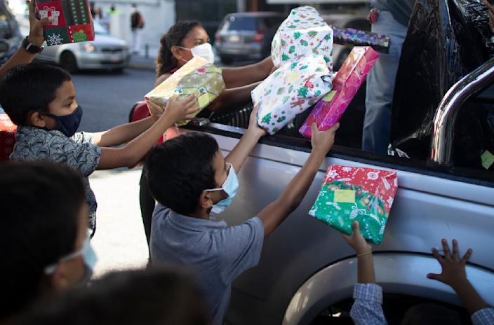 """Children receive Christmas presents donated by the volunteer group """"Un Juguete, Una Buena Noticia,"""" or One Toy, One Good News, from the back of a pick-up truck in Caracas, Venezuela, Friday, Dec. 18, 2020. The volunteer group is made up of journalists and other media workers who collect donations and hand out toys to poor children. (AP Photo/Ariana Cubillos)"""