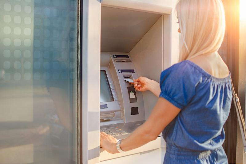 Young blond woman checking account balance, taking money from ATM outdoors