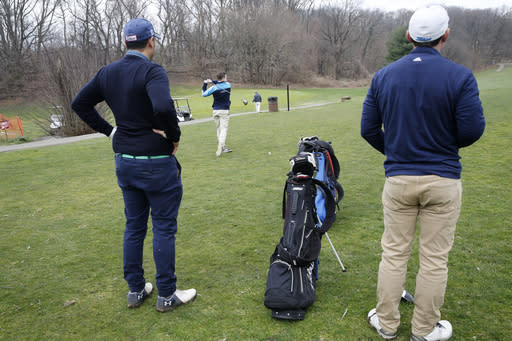 Two golfers watch another hit off the tee at Forest Park Golf Course, Friday, March 20, 2020, in New York. Even as the pandemic has shuttered restaurants, bars and beaches, many golf courses around the country have managed to stay open with all sorts of precautions in place to promote social distancing. (AP Photo/Kathy Willens)