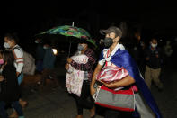 Migrants trying to reach the U.S. border walk before dawn along the highway leading to Choloma, Honduras, Thursday, Jan. 14, 2021. About 200 Honduran migrants resumed walking toward the border with Guatemala early Thursday, a day before a migrant caravan was scheduled to depart San Pedro Sula. (AP Photo/Delmer Martinez)