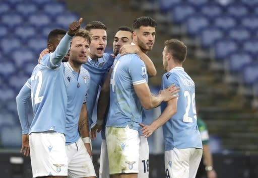 Lazio's Ciro Immobile, second left, celebrates after scoring his side's second goal during the Serie A soccer match between Lazio and Fiorentina at the Olympic Stadiumin Rome, Italy, Wednesday, Jan. 6, 2021. (AP Photo/Andrew Medichini)