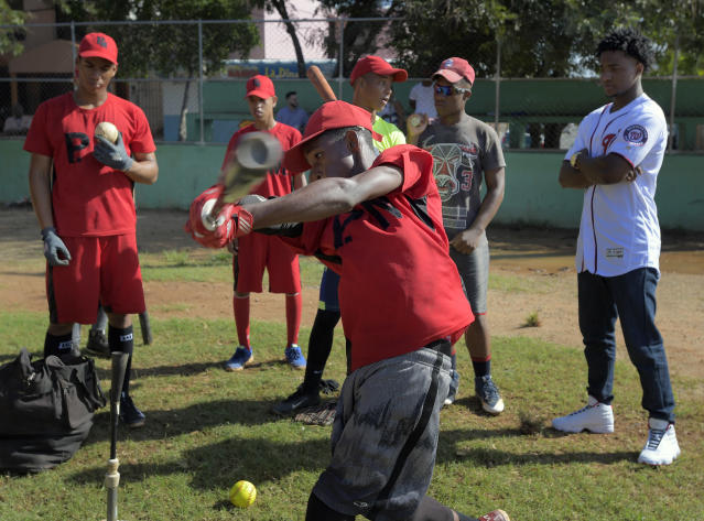 "Members of the baseball school called 'Los Cachorros de la Italia' conduct hitting practice with Victor Robles, right, watching. This was the school that <a class=""link rapid-noclick-resp"" href=""/mlb/teams/was"" data-ylk=""slk:Washington Nationals"">Washington Nationals</a> player Victor Robles was discovered in the Dominican Republic. (Getty Images)"