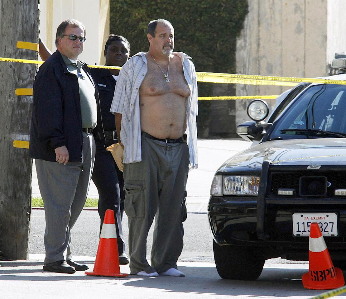 Police officers stand with a man who was being held in a patrol car at the scene of the arrest of a suspect near the Salon Meritage in Seal Beach, Calif., where a shooting left six people dead and three critically injured Wednesday, Oct. 12, 2011. (AP Photo/Reed Saxon)