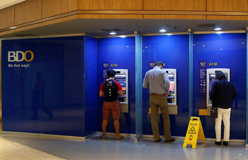 FILE PHOTO: BDO bank clients withdraw money from ATM machines in Makati, Metro Manila, Philippines August 2, 2016. REUTERS/Erik De Castro