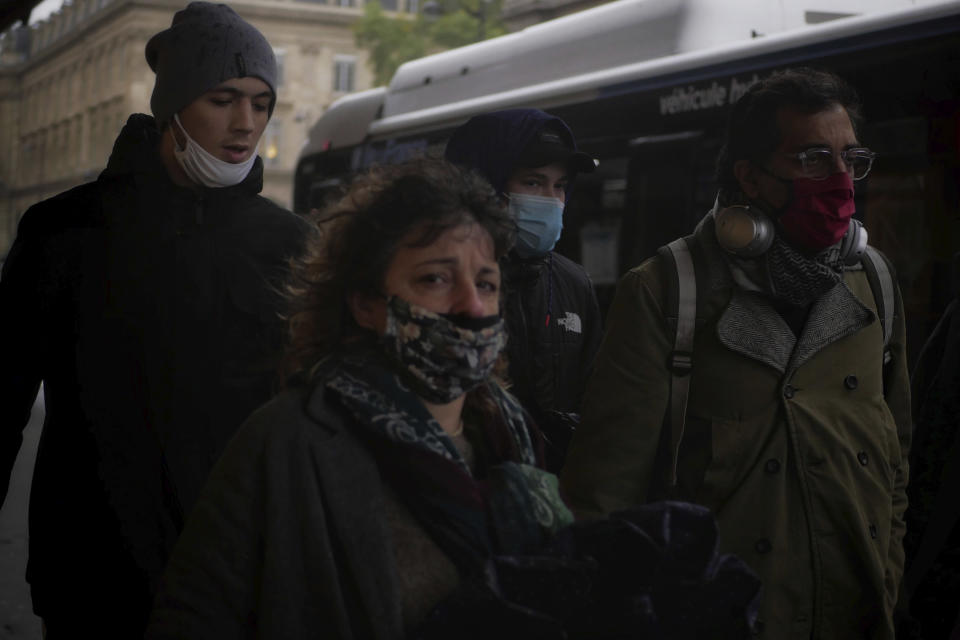 People wear masks as they walk in a street of Paris, Tuesday, Oct. 27, 2020. France's government is holding emergency virus control meetings Tuesday and warning of possible new lockdowns, as hospitals fill up with new COVID patients and doctors plead for backup. (AP Photo/Thibault Camus)