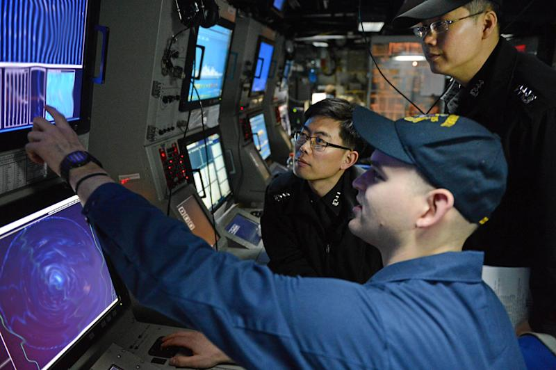 In this March 16, 2013 photo released by U.S. Navy,  Sonar Technician (Surface) 1st Class Andrew Murphy, foreground, works with South Korean Navy line officers in the sonar control room of the Arleigh Burke-class guided-missile destroyer USS McCampbell during an anti-submarine warfare exercise as part of exercise Foal Eagle 2013 in the West Sea, South Korea. (AP Photo/U.S. Navy, Mass Communication Specialist 3rd Class Declan Barnes)