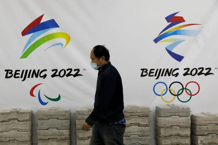 FILE PHOTO: Man walks past a board with logos of 2022 Winter Olympic Games, at a souvenir shop under renovation in Beijing