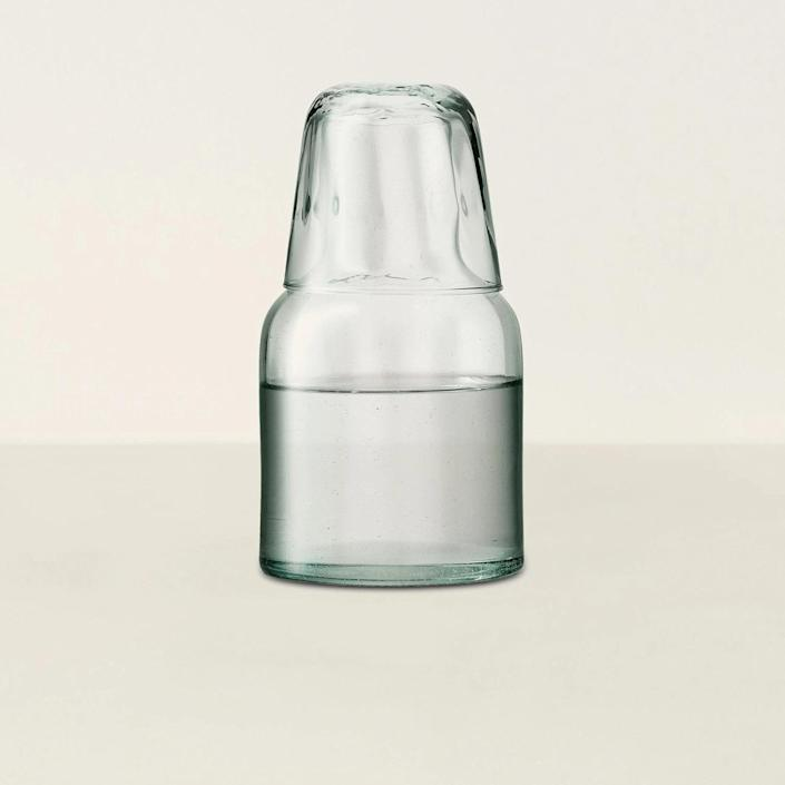 """Also made of recycled glass, this carafe from eco-friendly LSA International includes a fun nested tumbler handy for keeping cold water by your bedside or desktop all day long. The clear glass has a slight green tint. $42, Goodee. <a href=""""https://www.goodeeworld.com/collections/decanters-carafes/products/mia-carafe-tumbler"""" rel=""""nofollow noopener"""" target=""""_blank"""" data-ylk=""""slk:Get it now!"""" class=""""link rapid-noclick-resp"""">Get it now!</a>"""