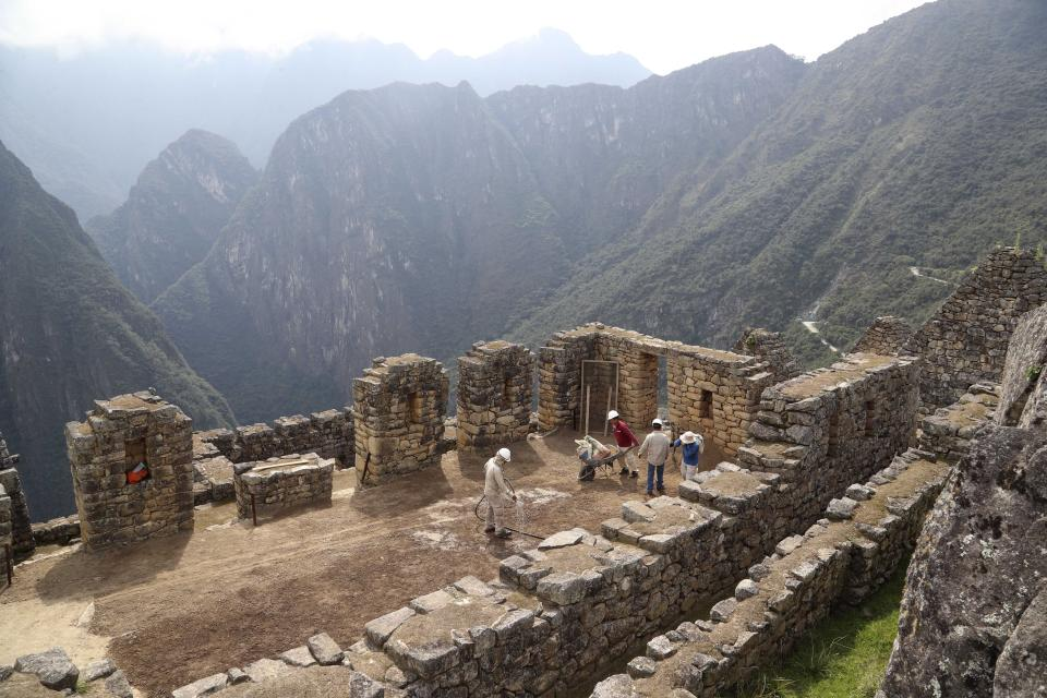 Maintenance workers clean the empty Machu Picchu archeological site that's closed to the public amid the COVID-19 pandemic in the department of Cusco, Peru, Tuesday, Oct. 27, 2020. The world-renown Incan citadel of Machu Picchu will reopen to the public on Nov. 1. (AP Photo/Martin Mejia)