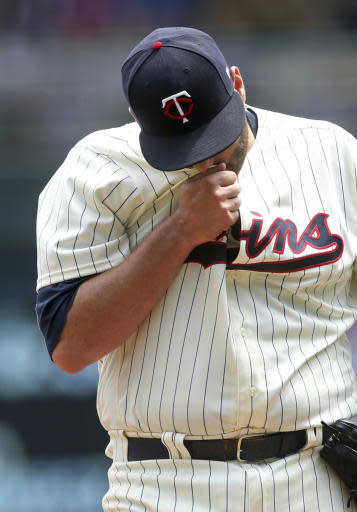 Minnesota Twins pitcher Lance Lynn wipes his face after giving up a solo home run to Kansas City Royals' Mike Moustakas in the third inning of a baseball game Wednesday, July 11, 2018, in Minneapolis. (AP Photo/Jim Mone)