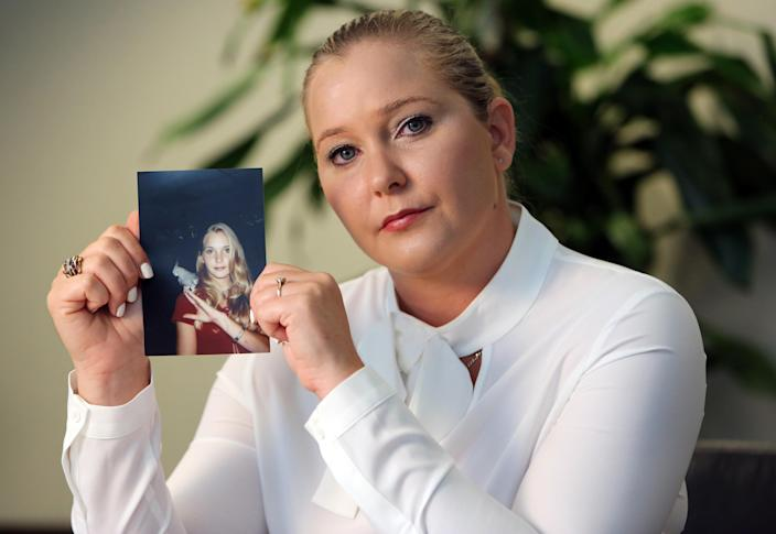 Virginia Giuffre holds a photo of herself at age 16, when she says Jeffrey Epstein began abusing her sexually. (Getty Images)
