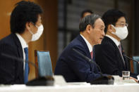 ADDS NAME OF PARTICIPANTS - Japanese Prime Minister Yoshihide Suga, center, announces that Tokyo, Kyoto and Okinawa will be applied for pre-emergency status under a new prevention law during a government task force meeting at the prime minister's office Friday, April 9, 2021, in Tokyo. Japan announced Friday that it will raise the coronavirus alert level in Tokyo to allow tougher measures to curb the rapid spread of a more contagious variant ahead of the Summer Olympics. Minister of Health, Labor and Welfare Norihisa Tamura, is at left, and Japan's Chief Cabinet Secretary Katsunobu Kato, is at right. (AP Photo/Eugene Hoshiko, Pool)