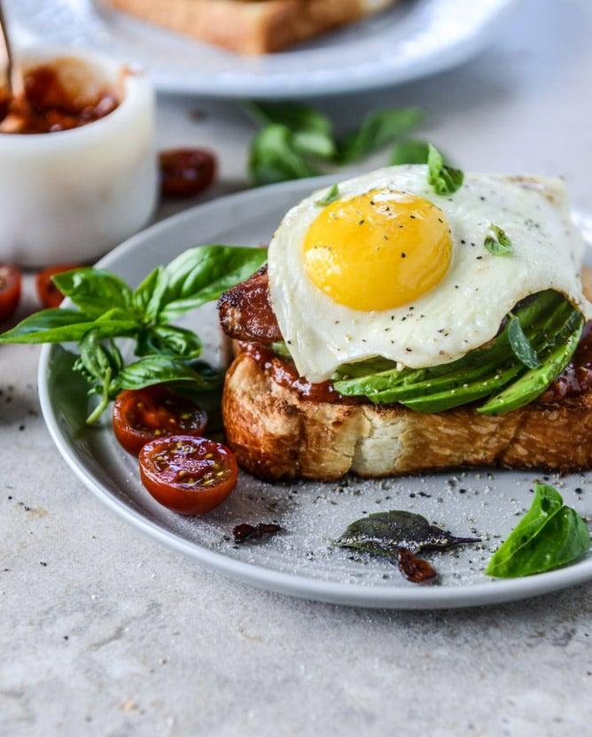 """<p><strong>Get the recipe:</strong> <a href=""""https://www.howsweeteats.com/2016/08/avocado-bacon-and-egg-toast-with-quick-tomato-jam/"""" target=""""_blank"""" class=""""ga-track"""" data-ga-category=""""Related"""" data-ga-label=""""https://www.howsweeteats.com/2016/08/avocado-bacon-and-egg-toast-with-quick-tomato-jam/"""" data-ga-action=""""In-Line Links"""">avocado toast with bacon and eggs</a>.</p>"""