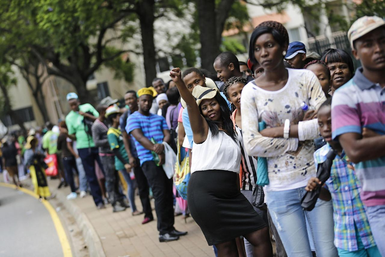 A young woman raises her fist as she queues with others wanting to pay their respects to Nelson Mandela in downtown Pretoria, South Africa, Friday, Dec. 13, 2013. Former South African President Nelson Mandela is on the third and final day of lying in state at the Union Buildings in Pretoria. (AP Photo/Markus Schreiber)