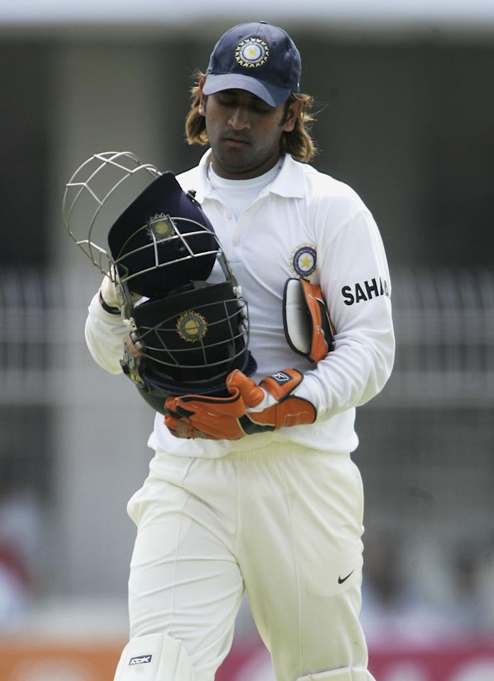 NAGPUR, INDIA - MARCH 02:  Mahendra Singh Doni of India carries the helmets during day two of the First Test between India and England at the VCA Stadium on March 2, 2006 in Nagpur, India.  (Photo by Tom Shaw/Getty Images)