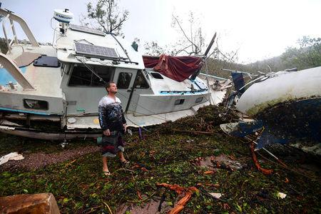 Local resident Bradley Mitchell inspects the damage to a relative's boat after it smashed against the bank after Cyclone Debbie passed athrough the township of Airlie Beach, located south of the northern Australian city of Townsville, March 29, 2017.    AAP/Dan Peled/via REUTERS
