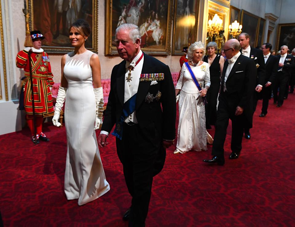 Melania Trump and the Prince of Wales arrive through the East Gallery during the State Banquet at Buckingham Palace, London. [Photo: PA]