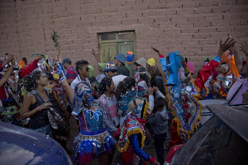 In this Feb. 25, 2017, photo, revelers dance during carnival celebrations in the remote Andean town of Uquia, Argentina. During the 9 days that the festivity lasts there, carnival revelers dressed as devils are not supposed to take their costumes off or reveal their identity. (AP Photo/Alvaro Medina)