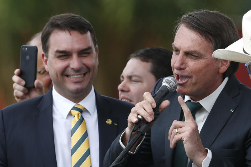 Accompanied by his son Sen. Flavio Bolsonaro, Brazil's President Jair Bolsonaro speaks at the launch of his new political party, Alliance for Brazil, in Brasilia, Brazil, Thursday, Nov. 21, 2019. At odds with the party leadership that nominated him for the presidency, Bolsonaro left the Social Liberal Party earlier this month and created his own. (AP Photo/Eraldo Peres)