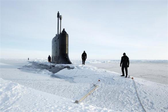 U.S. Navy safety swimmers stand on the deck of the Virginia class submarine USS New Hampshire after it surfaced through thin ice during exercises underneath ice in the Arctic Ocean north of Prudhoe Bay, Alaska March 19, 2011.