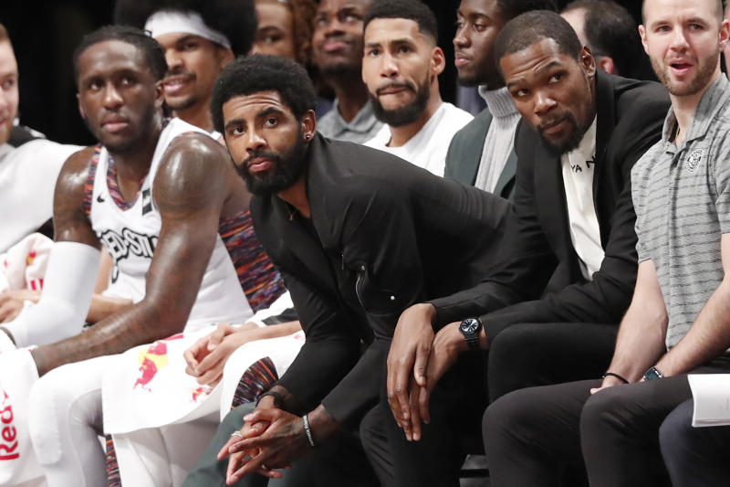 Injured Brooklyn Nets guard Kyrie Irving, center, perches on the edge of his seat during the second half of an NBA basketball gam against the New York Knicks, Thursday, Dec. 26, 2019, in New York. The Knicks defeated the Nets 94-82. (AP Photo/Kathy Willens)