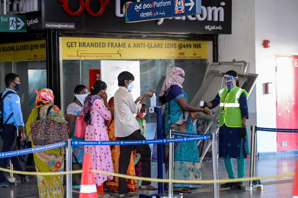 Passengers get their temperature checked as they arrive at a metro station following the resumption of train services after more than five months of shutdown due to the coronavirus pandemic, in Hyderabad on September 7, 2020. (Photo by NOAH SEELAM/AFP via Getty Images)