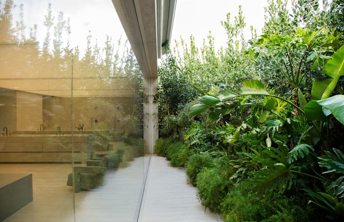 "<div class=""caption""> A lush garden by Wirtz International Landscape Architects shields the window-walled master bath. </div>"