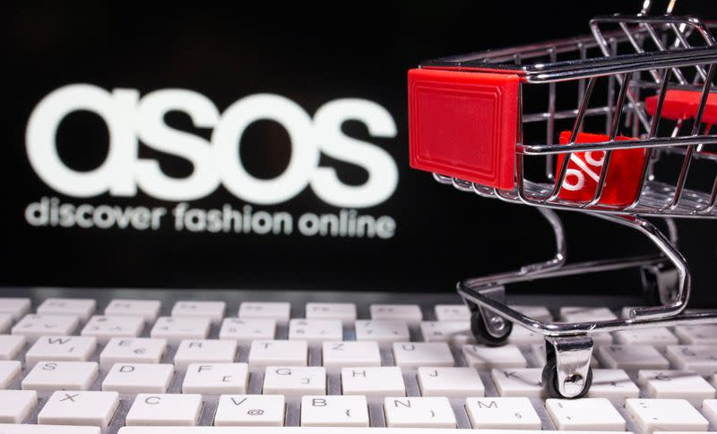 A keyboard and a shopping cart are seen in front of a displayed ASOS logo in this illustration picture
