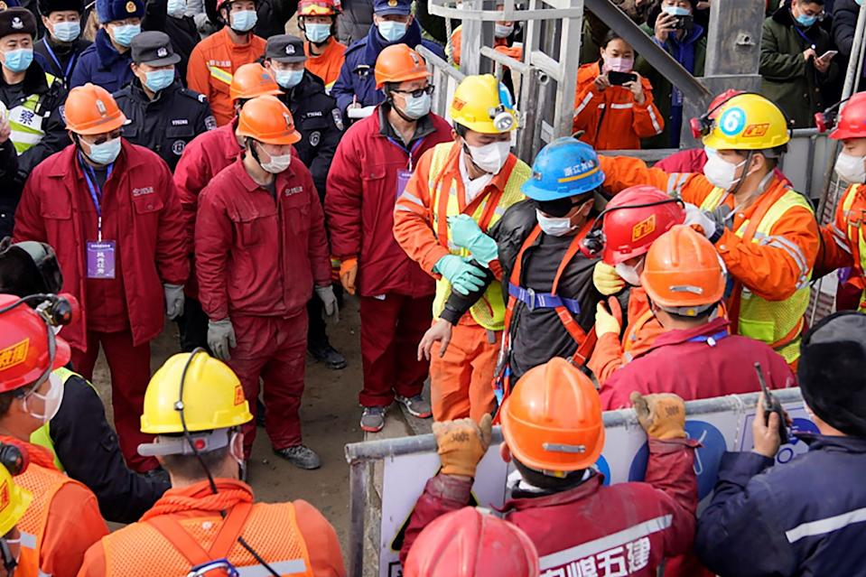 <p>One (blue helmet) of the 22 miners rescued from hundreds of metres underground in a gold mine in China</p> (CNS/AFP via Getty Images)