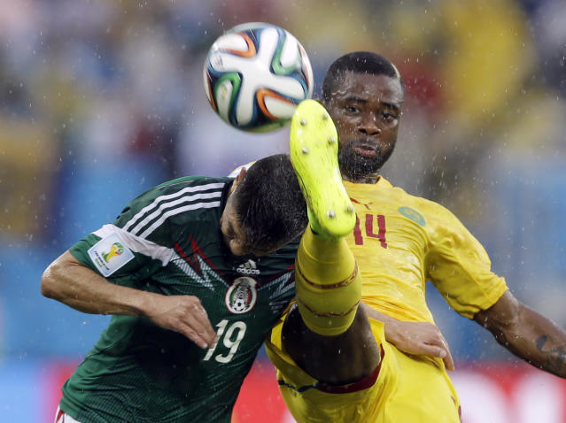 In this Friday, June 13, 2014 photo, Mexico's Oribe Peralta, left, and Cameroon's Aurelien Chedjou, battle for the ball during their group A World Cup soccer match in the Arena das Dunas in Natal, Brazil. Peralta scored in the 61st minute to help Mexico to a 1-0 victory Friday and the three points it needed to have any chance of advancing from a tough Group A at the World Cup. (AP Photo/Ricardo Mazalan)