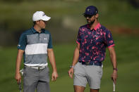 Jordan Spieth, left, talks with Michael Phelps while playing on the 12th green during the ProAm at the BMW Championship golf tournament, Wednesday, Aug. 25, 2021, at Caves Valley Golf Club in Owings Mills, Md. The BMW Championship tournament begins Thursday. (AP Photo/Julio Cortez)