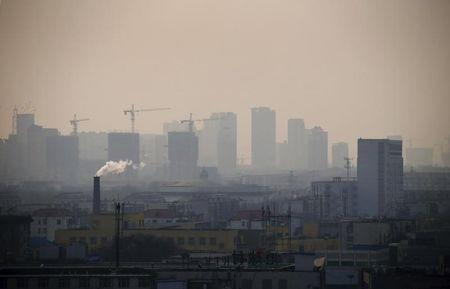 File photo of smoke rising from a chimney among houses as new high-rise residential buildings are seen under construction on a hazy day in the city centre of Tangshan