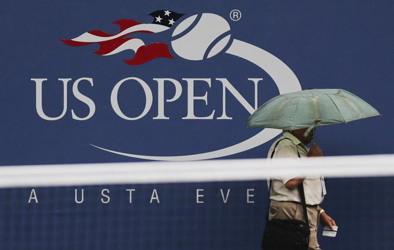 A person passes a logo for the US Open before play is to resume at the 2012 US Open tennis tournament, Saturday, Sept. 8, 2012, in New York. (AP Photo/Charles Krupa)