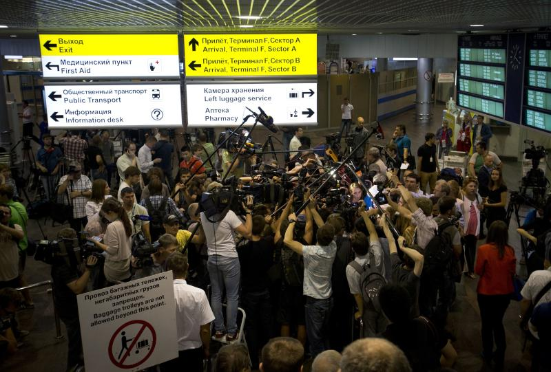 Journalists gather around Genri Reznik, a prominent lawyer and head of the Moscow bar association, at Sheremetyevo airport outside Moscow, Russia, Friday, July 12, 2013. Two prominent Russian human rights officials say they plan to meet on Friday with Edward Snowden, the leaker of U.S. National Security Agency secrets, after receiving an invitation calling them to Moscow's Sheremetyevo international airport. Reznik said he was invited and would try to attend. He was quoted by Interfax as saying he expected Snowden called for the meeting in order to seek asylum in Russia. Snowden is believed to have been stuck in the transit zone of Moscow's Sheremetyevo international airport since June 23. (AP Photo/Alexander Zemlianichenko)