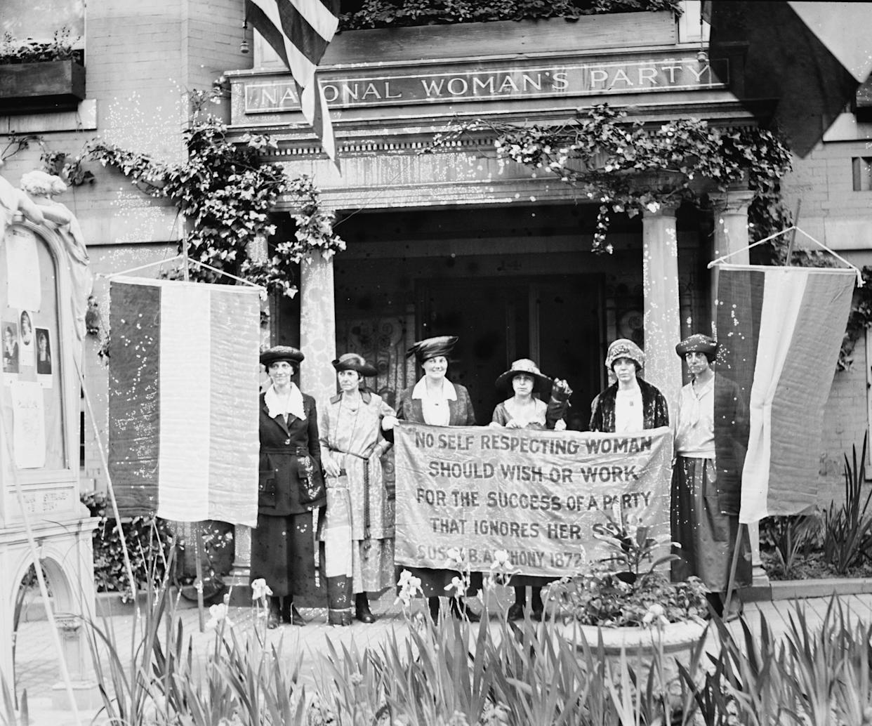 Suffragettes hold up banner in front of a building that has an architrave sign of the National Woman's Party circa 1918.