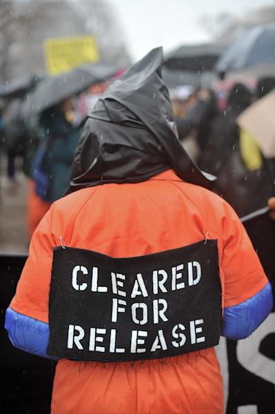 A protestor wears an orange detainee jumpsuit and a black hood in front of the White House in Washington on January 11, 2014 (AFP Photo/Nicholas Kamm)