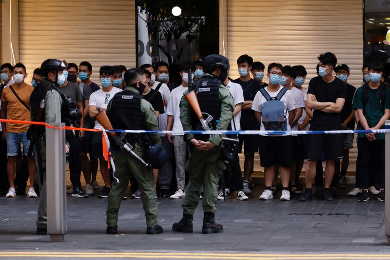 Riot police officers detain people during a protest in Hong Kong