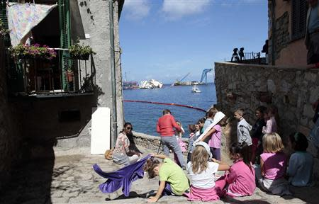 "Children look on at the capsized Costa Concordia cruise liner (background) after the start of the ""parbuckling"" operation outside Giglio harbour September 16, 2013. REUTERS/Tony Gentile"