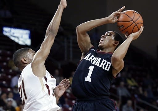 Harvard guard Siyani Chambers (1) shoots against Boston College guard Olivier Hanlan (21) during the first half of an NCAA basketball game in Boston, Tuesday, Dec. 4, 2012. (AP Photo/Elise Amendola)