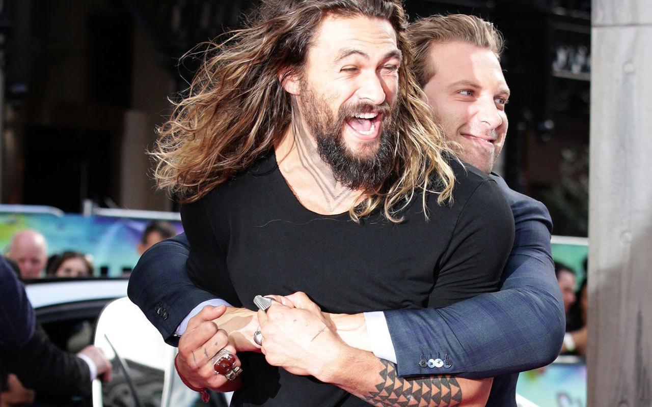 <p>Jai Courtney gave Jason Momoa a huge bear hug on the pink carpet.</p>